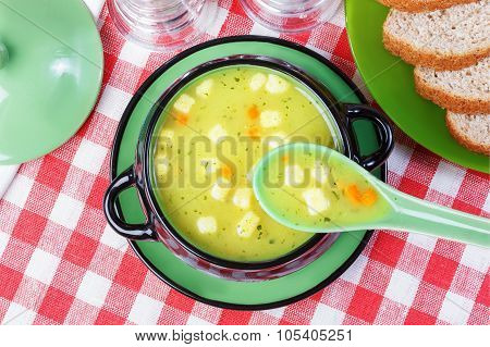 Soup With Croutons In A Tureen, Bread On A Plate, Napkin, Spoon On Red And White Tablecloth.