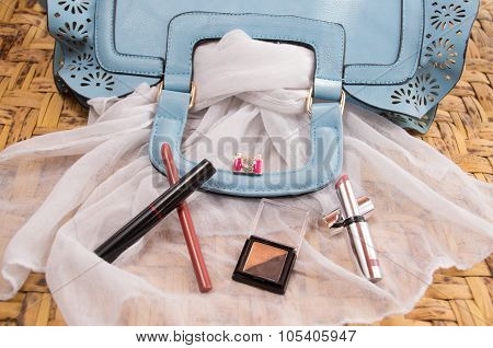 Womans purse light blue color lying flat with accessories such as mobile, makeup, keys and money spr