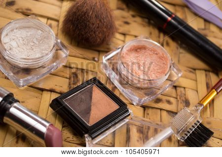 Womans purse accessories concept with makeup products spread out, closeup shot