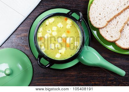 Soup Tureen In The Bread On A Plate, Napkin, On A Wooden Base.
