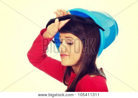 Confused woman holding empty blue plastic bucket.