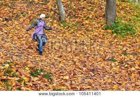 girl run in bright yellow autumn forest