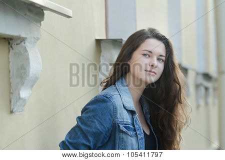 Urban portrait of looking away student girl in blue denim jacket leaning wall with architectural sto