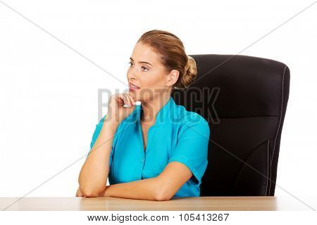 Young female doctor or nurse sitting behind the desk and talking with someone.