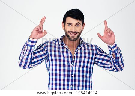 Portrait of a happy man standing with crossed fingers isolated on a white background