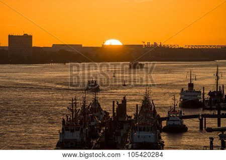 Various ships  in a harbor at sunset