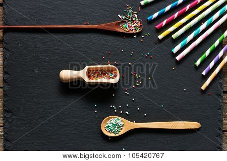 Drinking straws and sugar sprinkle dots on slate background