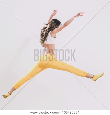 Young dancer woman jumping on a studio background. Healthy athletic woman is practicing dancing moves and jumps in the studio. Professional ballet dancer. Active sports lifestyle concept.