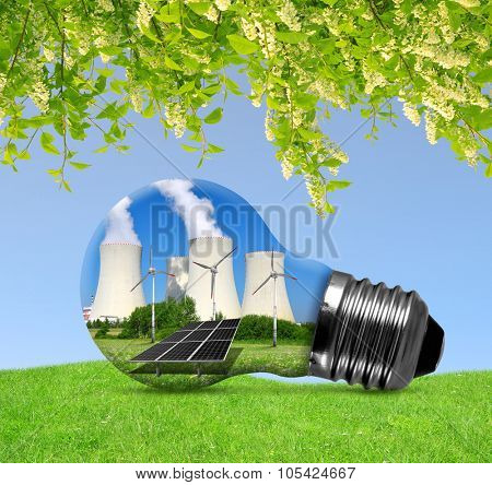 Nuclear power plant with solar panel and wind turbines in lightbulb. Energy resources concept.