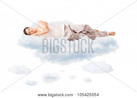 Young joyful man in pajamas sleeping on a cloud and dreaming isolated on white background