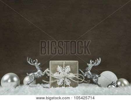 Wooden shabby style christmas background in silver, white, brown and grey colors with gift box and reindeer.