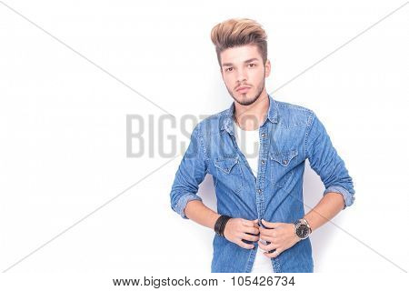 young casual man unbuttoning his jeans shirt on white studio background