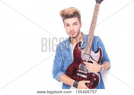 serious rocker holding red electric guitar and looks at the camera on white background