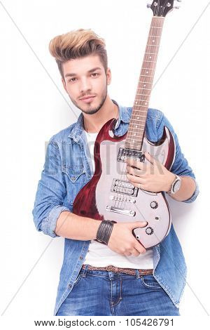 happy young guitarist holding his red electric guitar in his arms, on white studio background