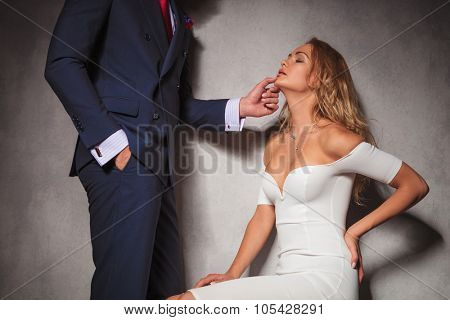 sexy picture of a gentleman holding his woman by her chin, she is sitting in studio. hot sensual couple in studio