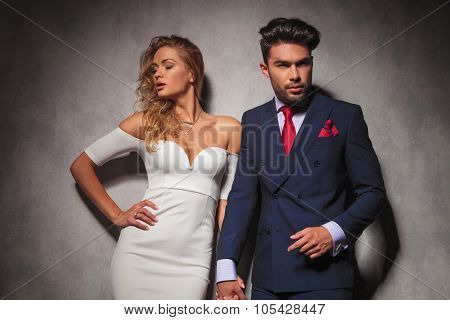 hot elegant couple holding hands and posing in studio, he is wearing a double breasted suit with red tie and she is wearing a white dress