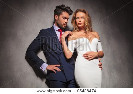 fashion elegant man embracing his woman and looks at her engagement ring , she is looking away from the camera with her hand on shoulder