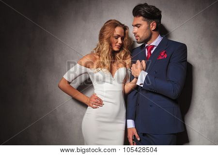 hot sexy elegant man holds his woman's hand, he is looking at her while she looks down, in studio