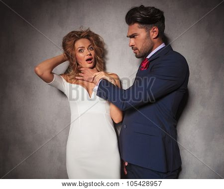 angry fashion elegant man with his hands around his woman's neck is choking her , they have problems