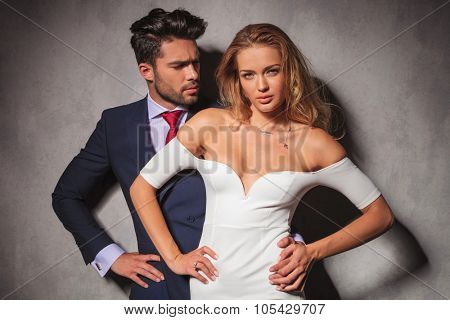 elegant man standing behind his woman with hands on hips. Fashion elegant couple in studio posing