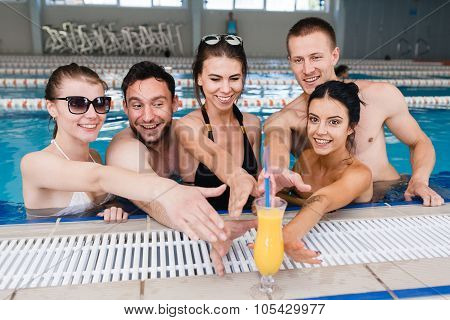 Friends having party and drinking buckets at a swimming pool