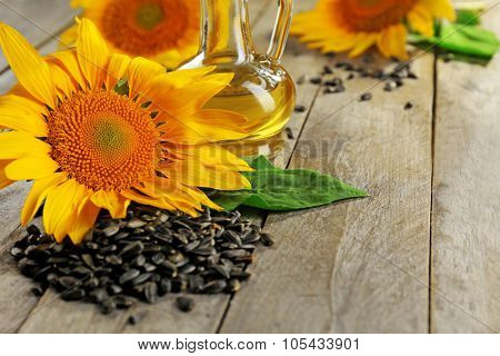 Beautiful bright sunflowers with seeds and bottle of oil on wooden table close up