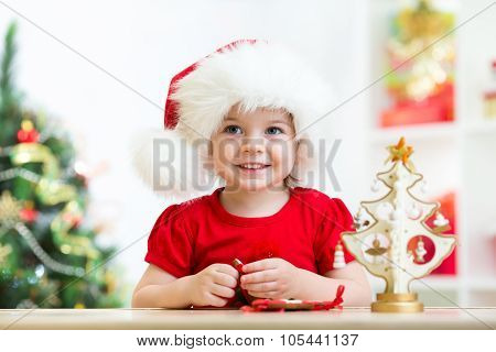 Little girl child wearing a festive red Santa hat with Christmas cookies