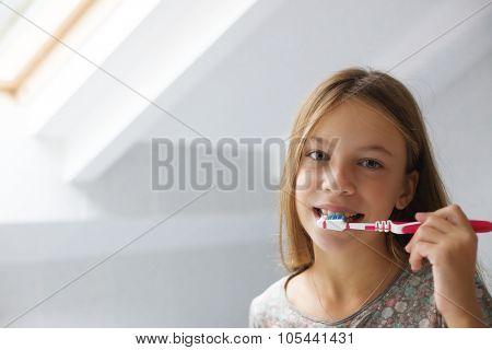 Pre teen girl brushes her teeth in the hotel bathroom