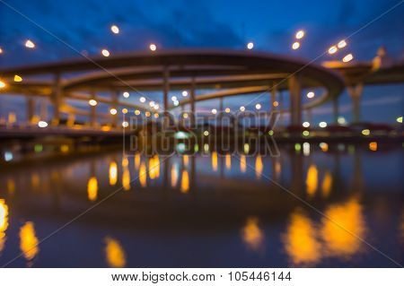 Abstract blurred bokeh Huge elevated crossroad during twilight with water reflection