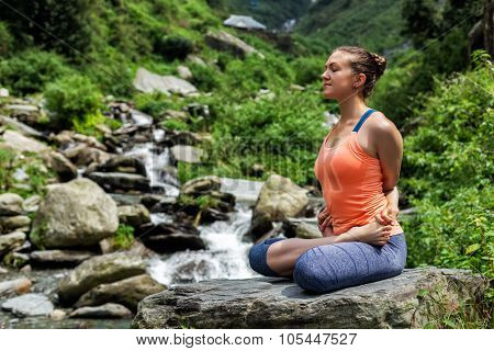 Young sporty fit woman doing yoga - meditating in Baddha Padmasana (Bound Lotus Pose) outdoors at tropical waterfall
