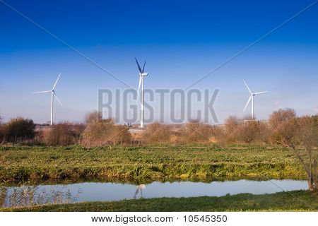 Three Wind Turbines In English Countryside  On  Blue Sky Autumn