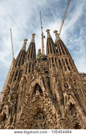 BARCELONA, SPAIN - MAY 02: Low Angle View of Exterior Facade of Sagrada Familia Church with Construction Cranes on Roof, Barcelona, Spain. May 02, 2015