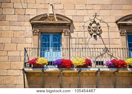 BARCELONA, SPAIN - MAY 02: Stone townhouse with Art Nouveau windows with carved architraves and an iron railing on the exterior balcony, Poble Espanyol, Barcelona, Spain. May 02, 2015