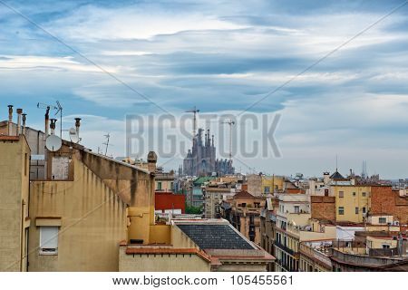 View of Sagrada Familia Church with Construction Cranes Underneath Overcast Sky, as seen from Rooftop of Casa Mila, Barcelona, Spain. May 02, 2015