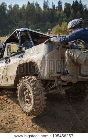 RUSSIA, PUSHKINO -?? 20 SEP, 2014: Rally team member is climbing on off-road vehicle at Rainforest Challenge Russia Autumn 2014 PRO-X.