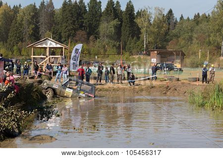 RUSSIA, PUSHKINO -?? 20 SEP, 2014: Off-road vehicle is driving in pond at Rainforest Challenge Russia Autumn 2014 PRO-X at sunny day.
