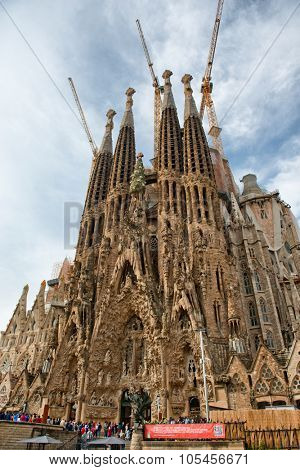 BARCELONA, SPAIN - MAY 02: Low Angle View of Facade Exterior of Sagrada Familia Church with Crowds of Tourists Gathered in Front, Barcelona, Spain. May 02, 2015.