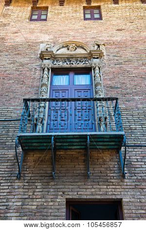 BARCELONA, SPAIN - MAY 02: Low Angle View of Balcony with Ornate Railing and Doorway on Exterior of Brick Building Wall, Barcelona, Spain. May 02, 2015.