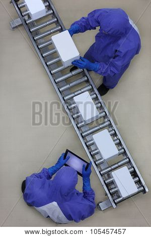 overhead view of two workers in blue uniforms working with boxes on packing line