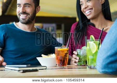 Closeup shot of young man and woman with cocktails. Friends drinking alcoholic beverages at cocktail party. Shallow depth of field with focus on cocktail glasses on table.
