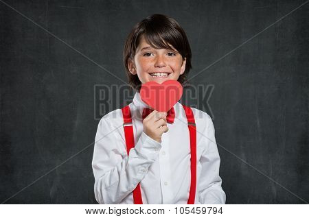 Little boy holding red heart. Portrait of lovable child smiling and looking at camera. Cute boy holding red heart isolated on blackboard with copyspace.
