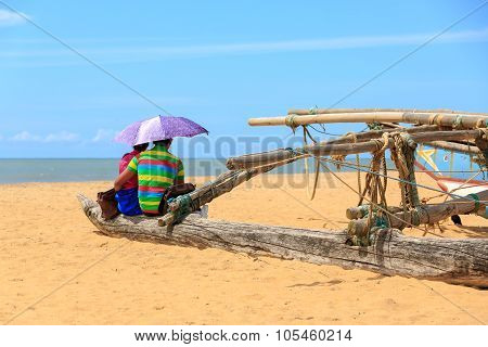 Young Couple Sitting At The Beach