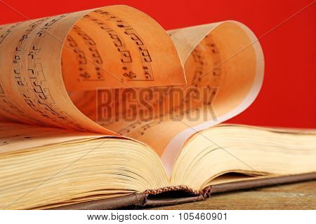Book pages curved into heart shape on red background