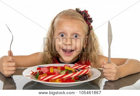 Pretty Little Female Child With Fork And Knife Eating Dish Full Of Candy Caramel And Sweet Food In S