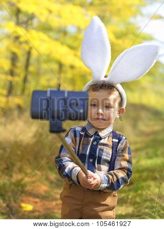 Funny Little Kid Boy With Easter Bunny Ears Taking A Selfie With A Selfie Stick