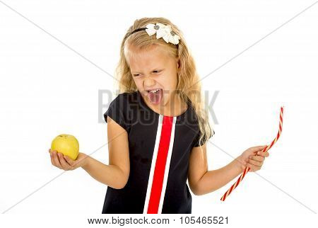 Little Pretty Female Child Choosing Dessert Holding Unhealthy But Tasty Red Candy Licorice And Apple