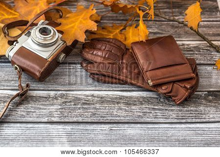 Leather Wallet And Luxurious Gloves With Camera On Vintage Background