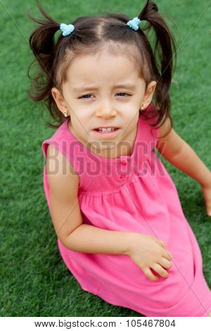Funny little girl with pigtails sitting on the grass