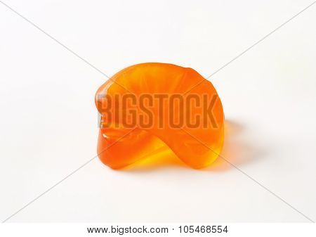 two orange fruit shaped gummy candies on white background