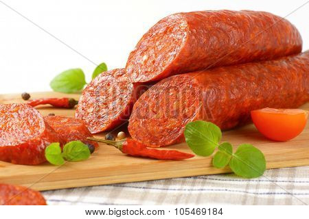close up of sliced pepperoni sausages on wooden cutting board